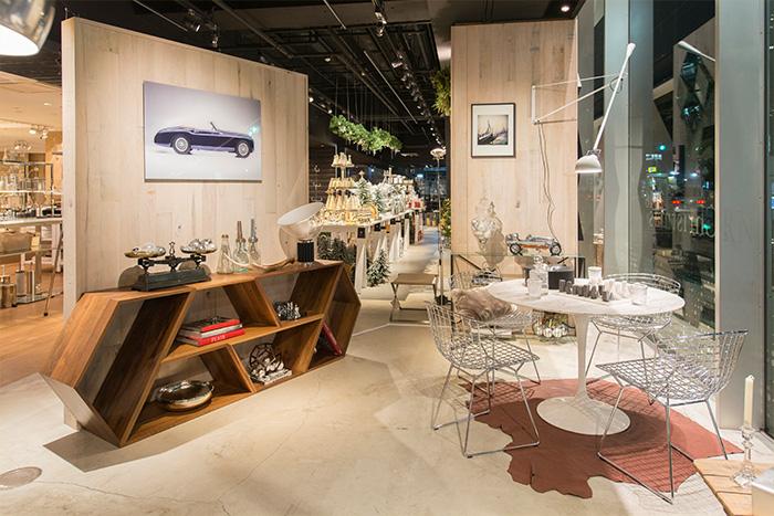 エーロ・サーリネンの上品なマット仕上げの大理石天板のテーブルに、ハリー・ベルトイアのサイドチェア、フロスのウォールランプ《265》を組み合わせたダイニングのセット。 幾何学的な造形が特徴的なメイドインラティオのシェルフはウォールナット材の仕様です。そして上の壁面にも、レネ・スタウドのクラシックカーを撮影したアートフォトを飾りました。ちなみにこちらは入り口に設置した板壁の裏側となります。