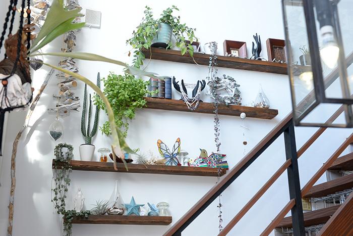 二階へ続く白い壁には、サイズ違いの棚にグリーンと小物を組み合わせ、動きのあるインテリアに。