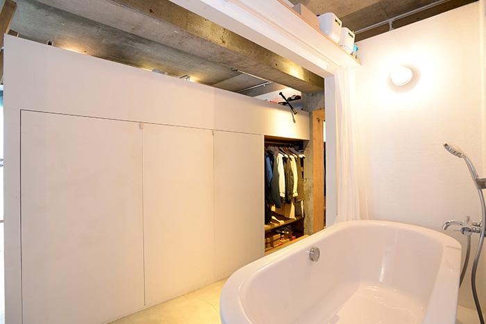 バスタブの前は全面収納。収納全体に扉を付けると圧迫感が出るので、一部オープン収納に。シャワーカーテンレールの上にも収納棚があります。