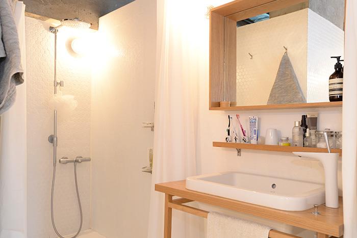 バスタブのすぐ脇にある洗面台の上には、フレームに物が置ける鏡と、小さなディスプレイ棚を設置。よく使うものを整理して、見られてもいい収納を心がけているそうです。
