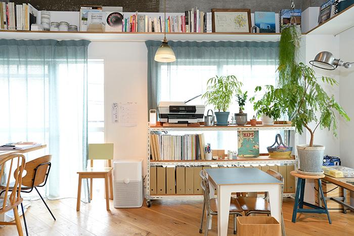 窓際の棚には、同じシリーズの書類ケースを揃えて、すっきりと。カーテンレール上の収納棚にも、絵や本が美しくディスプレイされています。