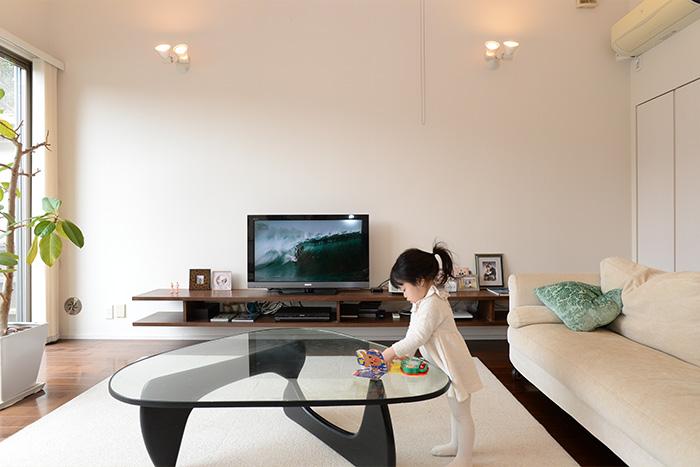 テレビ台は、角田さんが考案し、大工さんによる造作。デッキやリモコン類などがすっきりと納められている。家族写真も美しくディスプレイ。