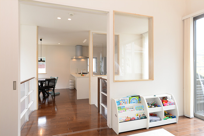 リビングとキッチンは、窓を介して、家族の気配が伝わります。子どもたちの本棚とおもちゃ箱も白で揃え、インテリアに連動感があります。